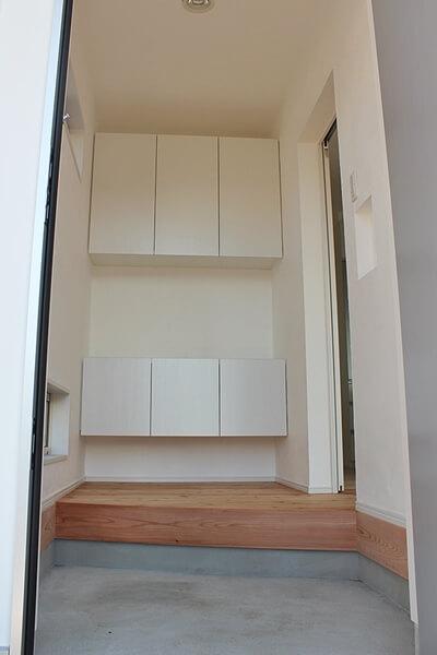 玄関内部。大容量の収納と白と木目のコントラストが美しい
